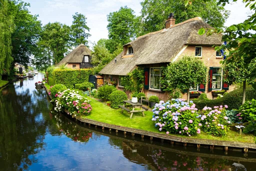 Landscape-view-of-famous-Giethoorn-village-with-canals-and-rustic-thatched-roof-houses-in-farm-area.-min
